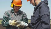 fosilní : engineers in uniform and gloves examine core extracted while drilling