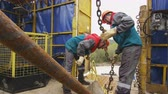 well site : workers control pipe lifting by oil exploratory drilling machine under cloudy