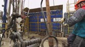 well site : workers draw out pipe and mount on exploratory drilling machine Stock Footage
