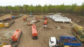 well site : aerial large building site on ground with vehicles trucks cranes at forest