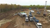 well site : bird-eye flight above site on brown territory with vehicles against birches Stock Footage