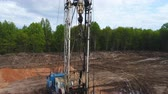 well site : exploratory drilling machine lifts up pipe to drill on prospecting site Stock Footage