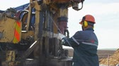 well site : employee inserts pipe into lifting mechanism of drilling machine Stock Footage