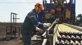 well site : worker prepares pipe for adjusting on drilling machine at prospecting site Stock Footage