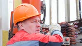 well site : worker in orange helmet controls with levers exploratory drilling machine Stock Footage