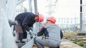 vezető : workers operate with electric drill on transformer substation building site
