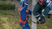 конкурент : KAZAN, TATARSTAN  RUSSIA - MAY 23 2018: Competitor in outfit climbs pole with leg-irons to save electrician mannequin at rescue team on May 23 in Kazan