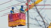 vesta : electricians install wires on transmission post in hanging crane cradle