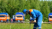 bobina : employee winds and fixes striped red tape fencing on metal pylon
