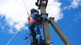 instalator : electrician-fitter climbs pole with leg-irons holding mannequin rescueing