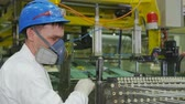 operador : close worker in uniform and respirator adjusts thread tension in workshop