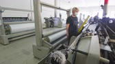 sintético : woman monitors looms operation at synthetic fabric manufacturing factory