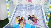 pony : animator in blue pony suit plays with children on slide