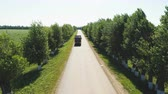 road top view : rural track with trees on sides and driving cars against sky