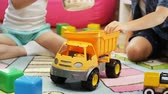 украшать : kids play with yellow tipper truck and toy pan in children room Стоковые видеозаписи