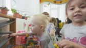 pigtails : close view cute children play with bright colored toys Stock Footage