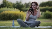 hidratar : beautiful woman drinking water after training and listening to music with your smartphone