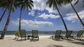 Tropical beach, perfect place for relaxing, sun recliner in the shade of a palm tree.