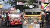 time : LEGAZPI, PHILIPPINES - MARCH 17 2014: Jeepneys passing, Filipino inexpensive bus service. Jeepneys are the most popular means of public transportation in the Philippines. Stock Footage