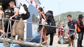 ada : PHANGAN,THAILAND - JANUARY 17,2014 :Unidentified tourists boarding a boat from the island Phangan, where there was a full moon party.The event now attracts anywhere from 40,000 party-goers on a month