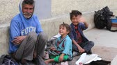 men : LEH, INDIA - SEPTEMBER 08 2014: An unidentified beggar family begs for money from a passerby in Leh. Poverty is a major issue in India
