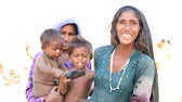 bebês : PUSHKAR, INDIA - OCTOBER 23 2014: An unidentified beggar women and children begs for money from a passerby in Pushkar. Poverty is a major issue in India