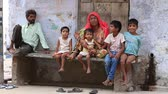 bebês : PUSHKAR, INDIA - OCTOBER 25, 2014: An unidentified Indian family sits on the street begs for money from a passerby in Pushkar. Poverty is a major issue in India