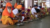 chapati : AMRITSAR, INDIA - SEPTEMBER 27, 2014: Unidentified poor indian people eating free food at a soup kitchen in the Golden Temple Stock Footage