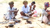 chapati : PUSHKAR INDIA OCTOBER 26 2014: Unidentified Indian men prepare a meal on a campfire during Pushkar Camel Mela. This fair is the largest camel trading fair in the world. Stock Footage