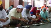 щедрость : AMRITSAR, INDIA - SEPTEMBER 29, 2014: Unidentified poor indian people receive a free meal inside the langar, a communal kitchen on the famous Sikh Golden Temple complex in Amritsar. Стоковые видеозаписи