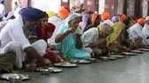 chapati : AMRITSAR, INDIA - SEPTEMBER 29, 2014: Unidentified poor indian people receive a free meal inside the langar, a communal kitchen on the famous Sikh Golden Temple complex in Amritsar. Stock Footage