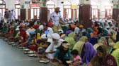 chapati : AMRITSAR, INDIA - SEPTEMBER 26, 2014: Unidentified poor indian people eating free food at a soup kitchen in the Golden Temple