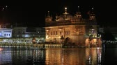 golden : AMRITSAR, INDIA - SEPTEMBER 28, 2014: Unidentified sikhs and indian people visiting the Golden Temple in Amritsar at night. Sikh pilgrims travel from all over India to pray at this holy site.