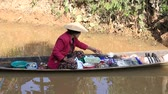 bugigangas : INLE LAKE, MYANMAR - JANUARY 12, 2016: Unidentified Burmese woman on small long wooden boat selling souvenirs, trinkets and bijouterieat the floating market on Inle Lake, Myanmar