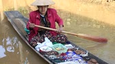 bugiganga : INLE LAKE, MYANMAR - JANUARY 12, 2016: Unidentified Burmese woman on small long wooden boat selling souvenirs, trinkets and bijouterieat the floating market on Inle Lake, Myanmar