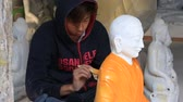 artesanato : MANDALAY, MYANMAR - JANUARY 17, 2016: Burmese man paints a marble statue of Buddha in the orange color in the workshop