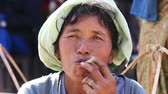 smoke : INLE LAKE, MYANMAR - JANUARY 12, 2016: Unidentified Burmese old woman smoking a big handmade cigar. Footage taken in a little village, where a woman does cigars by herself and smoke them proudly Stock Footage