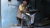 artesanato : DEVPRAYAG, INDIA - OCTOBER 13, 2014: Unidentified street tailor working on a foot sewing machine
