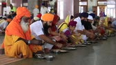 chapati : AMRITSAR, INDIA - SEPTEMBER 27, 2014: Unidentified poor indian people eating free food at a soup kitchen in the Sikh Golden Temple