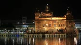 light : AMRITSAR, INDIA - SEPTEMBER 28, 2014: Unidentified sikhs and indian people visiting the Golden Temple in Amritsar at night. Sikh pilgrims travel from all over India to pray at this holy site.