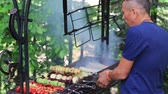 meia idade : Middle-aged man is preparing shish kebabs from vegetables on a grill in nature, close up. The concept of a healthy lifestyle. Stock Footage