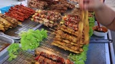 ás : KOH PHANGAN, THAILAND - FEBRUARY 15, 2018: Street food: thai vendor sells pork or chicken skewers, bbq fried meat on sticks, fry fish, seafood at night food market in island Koh Phangan, Thailand