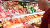refrigerador : KOH PHANGAN, THAILAND - MARCH 01, 2018: Man chooses products in the supermarket in the meat of the dairy department Koh Phangan, Thailand