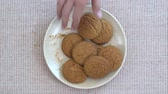 alcançando : Plate full of oatmeal cookies being snatched up by four hungry children. Close up, top view, macro Vídeos