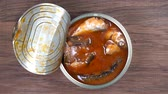 befőz : Using fork takes a sprats fish, sardines in tomato sauce from a tin can. Top view, close up, macro
