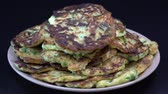 оладья : Vegetable pancakes from zucchini on black background, close up, rotates. Traditional Ukrainian cuisine