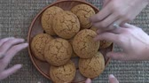 Plate full of oatmeal cookies being snatched up by four hungry children girls. Close up, top view, macro
