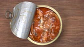 conservado : Using fork takes a sprats fish, sardines in tomato sauce from a tin can. Top view, close up, macro
