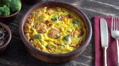 omelete : Ceramic bowl with vegetable frittata, simple vegetarian food. Frittata with egg, tomato, pepper, onion, broccoli and cheese on wooden table, close up. Italian egg omelette, rotates
