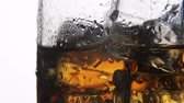 alkoholik : whiskey in a glass with ice on a light background in the contour light. Alcoholic beverages. video rotation